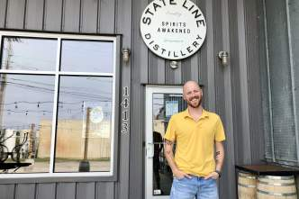 A man poses in front of State Line Distillery