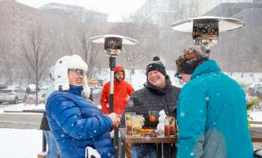 Three people enjoy drinks outdoors by heaters during a winter snowfall