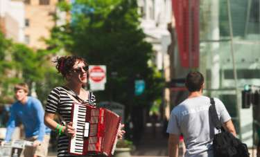 A woman playing the accordion on State Street