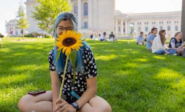 A woman with blue hair sits on the Wisconsin State Capitol lawn holding a sunflower