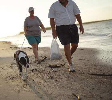 a man and woman walking a dog on the beach carrying a trash bag