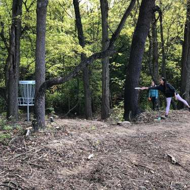 Two Women Playing Disc Golf in Wooded Area at Caesar's Ford Reserve in Jamestown, Ohio