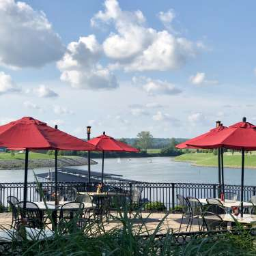 outdoor restaurant seating overlooking a marina and river