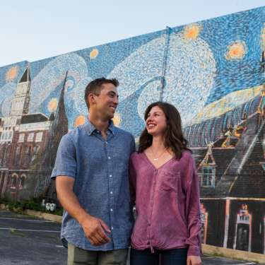 man and woman in front of a large mural