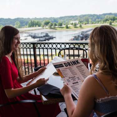 two ladies dining overlooking a marina