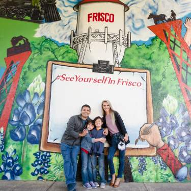 Family of four posing infront of the mural in the Rail District