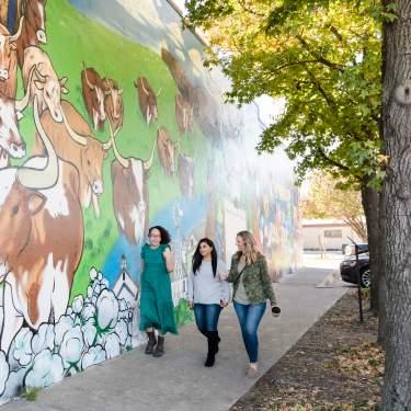 Three women walking in the Rail District