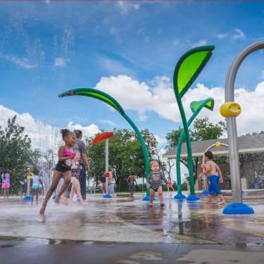 Children running around as water sprays around them on a splash pad