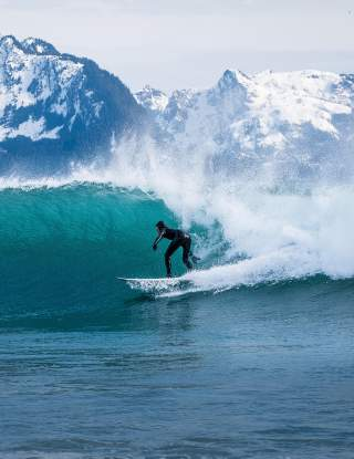 A surfer rides a wave with mountains in the background.