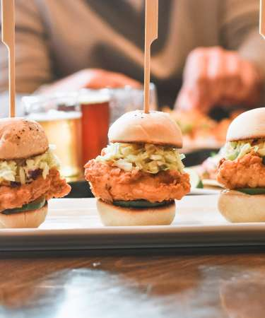 chicken sliders with people eating in the background