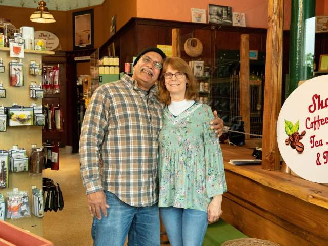 Owners of Shas Coffee standing in store, smiling