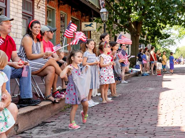 Kids waving flags at Riverfest Parade