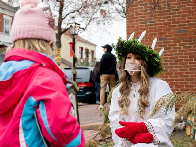 Character Santa Lucia talking with girl