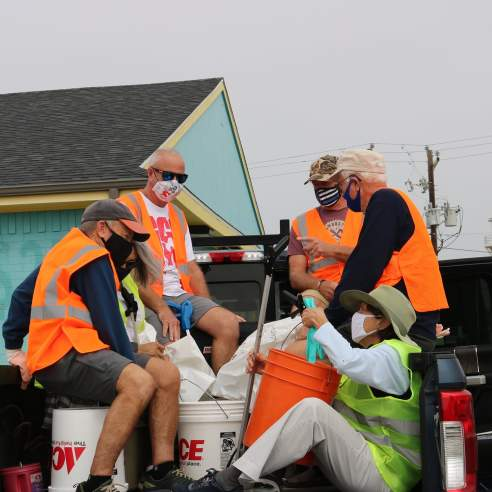 A group of five volunteers in orange safety vests sit in the bed of a truck with trash bags and buckets