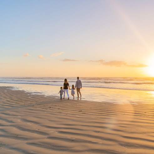 A family of four walks on the beach away from the camera towards the left. The sun is rising to the right.
