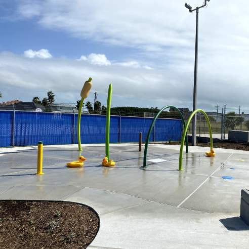 On a gray pad sits several green and yellow hoops and poles with water for kids to splash on. A playground is in the back right.