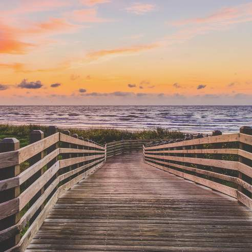 A wooden boardwalk leading to the beach at sunrise