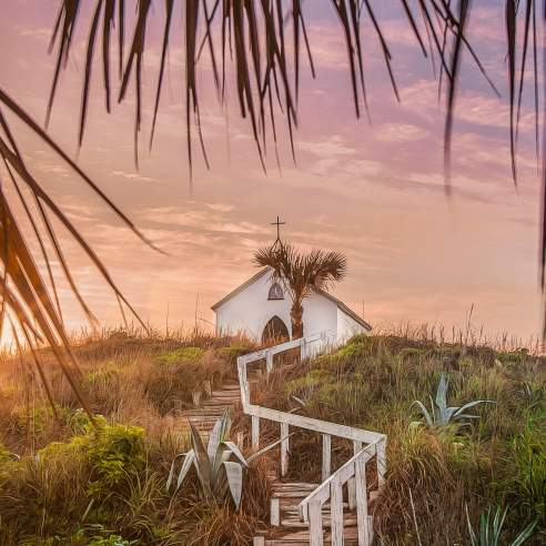 On top of a grassy hill at sunset sits a small white chapel topped with a cross. Steps with a white railing lead up to the chapel and palm tree fronds frame the photo