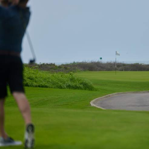The left side of the photo shows an unfocused man dressed in black golf clothes swinging a club. The rest of the photo is a manicured golf course with a flag in the center and the sea in the background