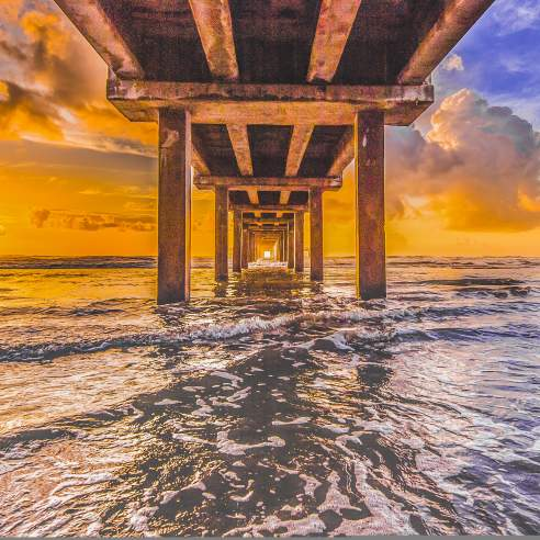 The sun rises just over the water from the perspective of under a pier