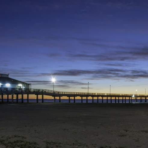 A fishing pier at dawn from the beach perspective as the sun breaks