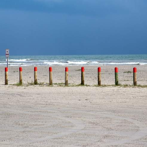 Bollards with a red top in the middle ground with blue water behind and sand in front