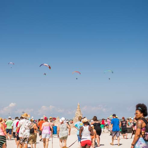 A crowd walks towards a giant sand sculpture with four parasails overhead