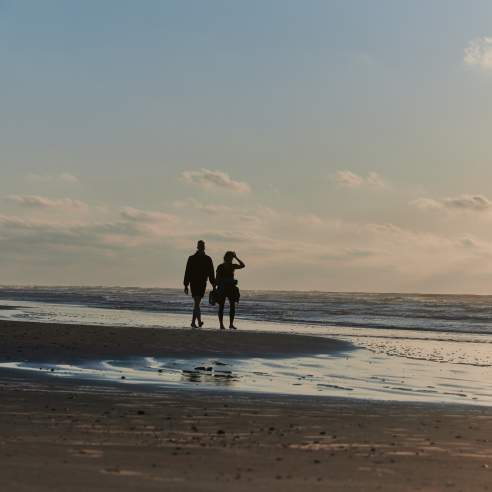A silhouetted couple walks along the beach