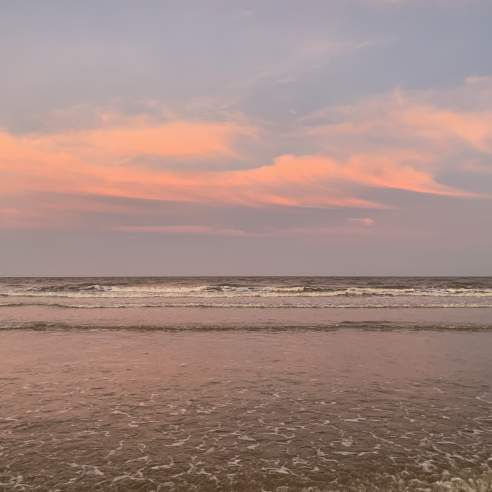A pink and blue sunset sky reflects off the water on the beach
