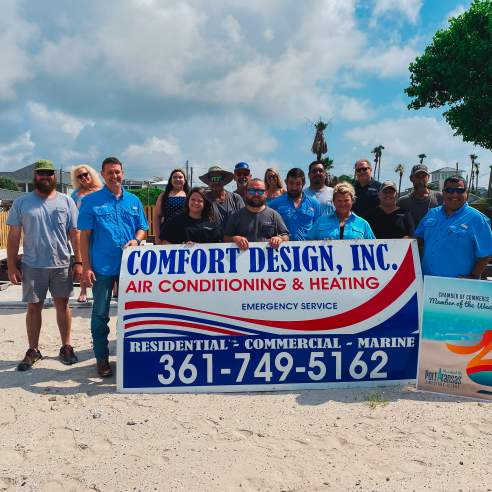 """A group of people stand behind and around a large red, white, and blue sign reading """"Comfort Design, Inc"""" with other details of the business below."""