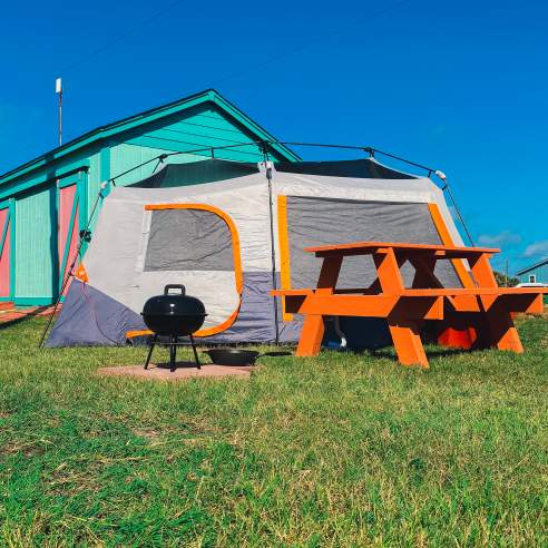 Gray and orange tent sits on grass next to an orange picnic table and black camp grill