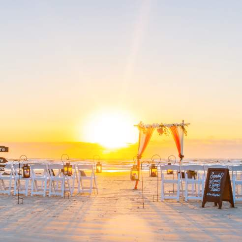 The sun rises on a wedding ceremony setup on the beach. There are rows of white chairs, wooden signs, and a tulle/floral arch.