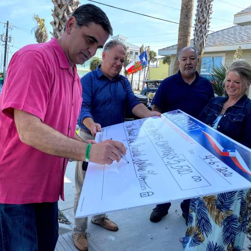 A man in a pink shirt signs a giant check while three others hold it up.