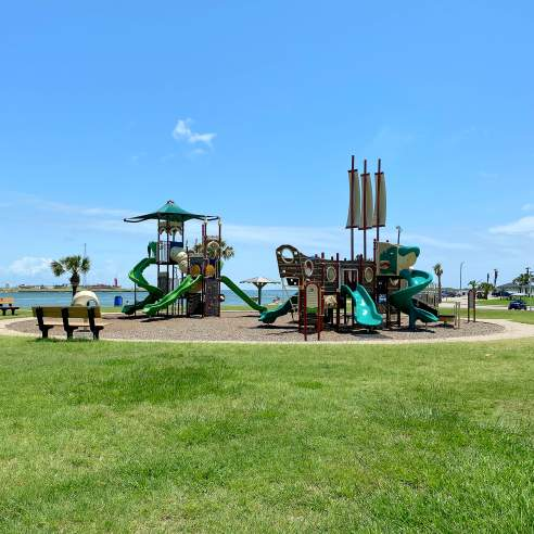A round gravel area surrounded by lush green grass holds a large playground. The playground is green and brown with slides, ship sails, and more. Water is in the background.