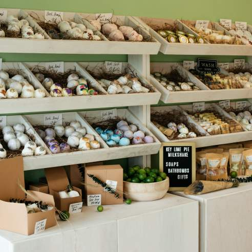 """Large gold letters reading """"KLPM"""" are hung on a green wall. Below the letters are three rows of shelving holding bath bombs nestled in crinkled paper. Cabinets hold up these shelves, and on the cabinets are more cosmetic products and a sign reading """"Key Lime Pie Milkshake, soaps, bath bombs, gifts"""""""