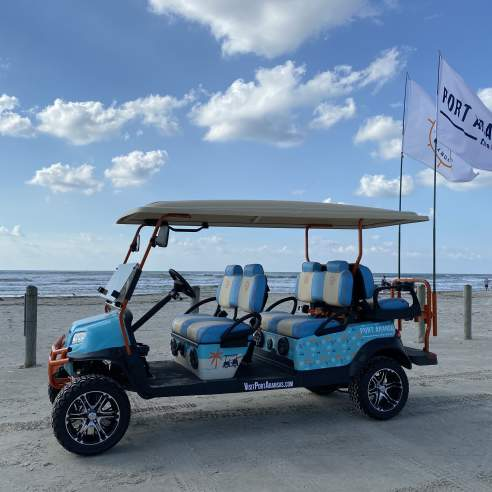 A light blue and patterned golf cart with two large flags sits on the beach.
