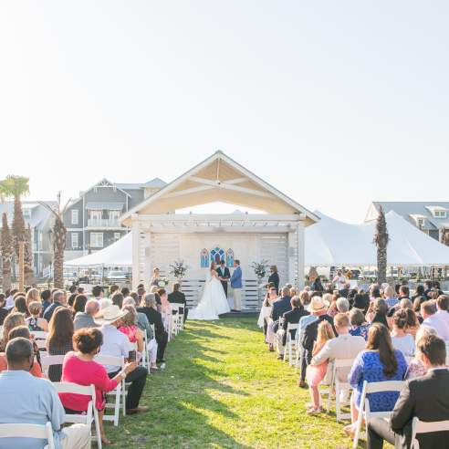 Photo of a crowd watching a couple say vows at outdoor wedding