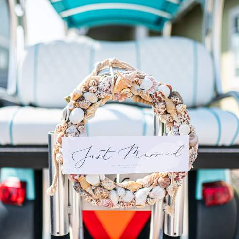 """In focus is a wreath made of seashells with a placard reading """"Just Married"""" in script font. The wreath is attached to the back of an out-of-focus turquoise golf cart"""