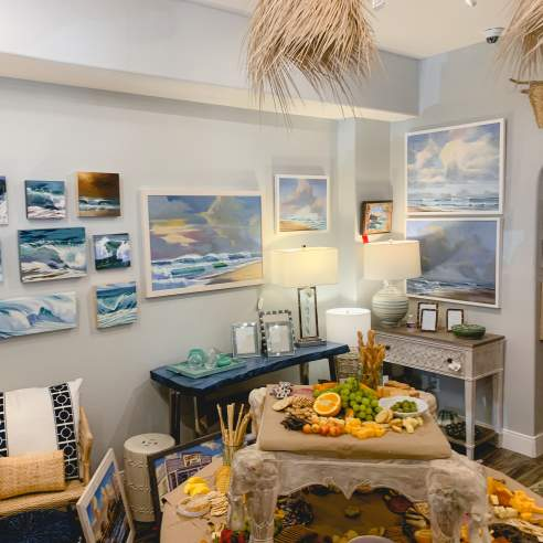 A round table of refreshments sits in front of a wall covered in ocean art, lit softly by table lamps