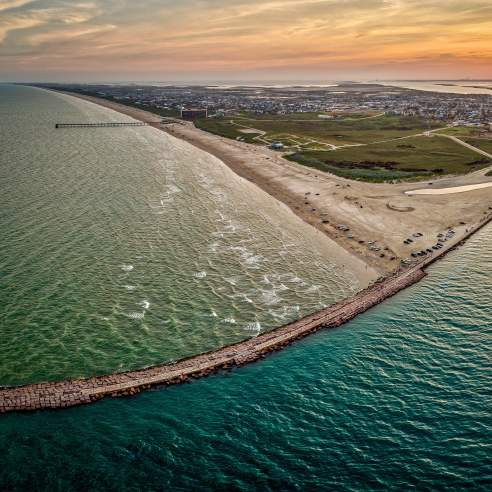 An aerial view of the coast showing the jetties in a teal water with the sun setting in the distance