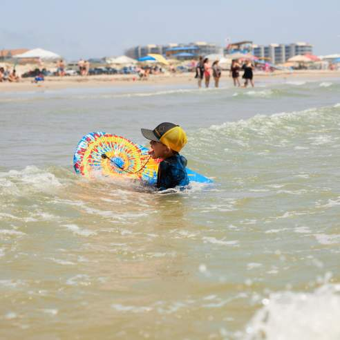 A child in a ball cap swims with a tie-dye boogie board near the beach