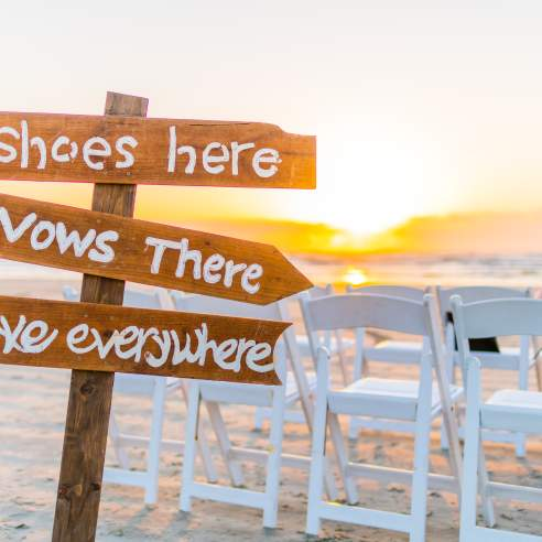 """A brown sign is stuck in the sand. It reads """"Shoes here,"""" """"Vows there,"""" and """"Love everywhere."""""""