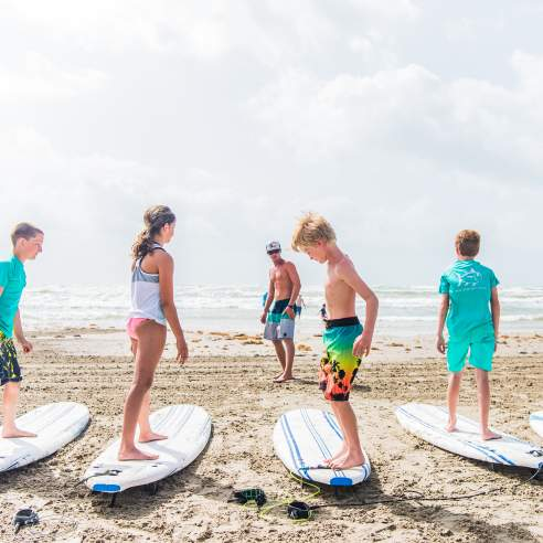 A group of five kids stand on surf boards resting on the sand while an instructor stands in front of them