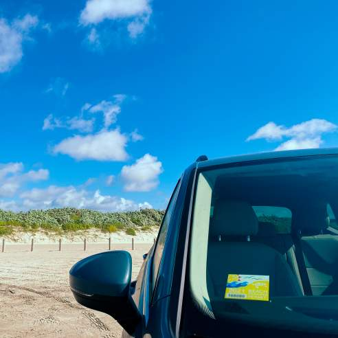 The left side shows blue sky with dunes and sand, right side is the front of a car with a yellow sticker on the windshield