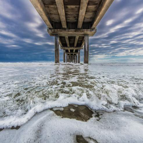 Foamy seawater rushes underneath a pier with a bright, cloudy sky