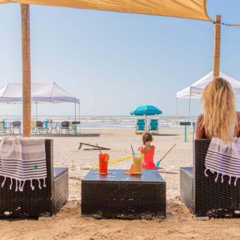 Two chairs on the beach are seen from the back. A blonde women sits in one chair and a table with tropical drinks sits between the chairs. A child plays in the sand in front of the setup.