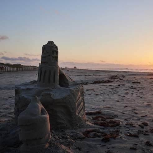 A sandcastle on the beach with the sun rising on the horizon