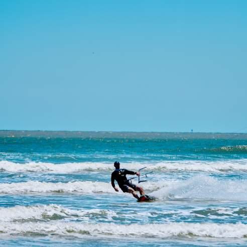 Man kite boards on blue water