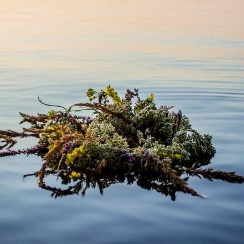 A wildflower wreath floats in a serene sea