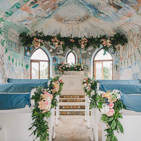 The interior of a chapel painted with murals is decorated with pink, white, and green florals, and white pews are draped in light blue fabric